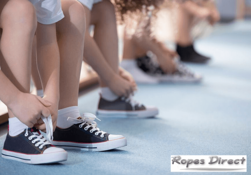 Children putting on trainers to play with tug of war ropes