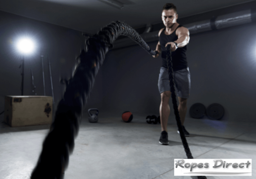 Man using battle ropes at home